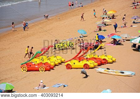 Albufeira, Portugal - June 10, 2017 - Tourists Relaxing On The Sandy Beach With Colourful Pedaloes I