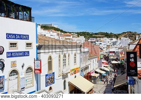 Albufeira, Portugal - June 10, 2017 - Elevated View Of Tourists Walking Along The Rua 5 Octubro Shop