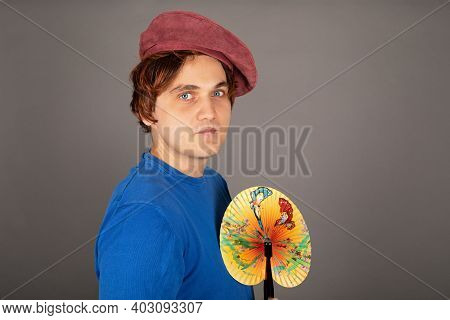 Portrait Of A Feminine Young Guy With Wig And Hat Holding A Colorful Fan In Front Of Grey Background