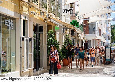 Faro, Portugal - June 12, 2017 - Tourists Walking Along The R De Santo Antonio Lined With Restaurant