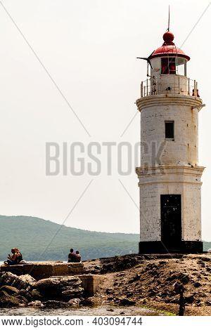 Vladivostok, Russia - July 30, 2015: Tourists Resting Near Lighthouse. The Old Japanese Lighthouse E