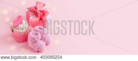 Cute Newborn Baby Girl Shoes With Festive Decoration Cupcake And Gift Box  Over Pink Background. Bab