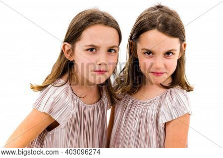 Identical Twin Girls Sisters Are Posing For The Camera.