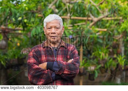 Portrait Of Elderly Asian Man Arms Crossed, Smiling And Looking At The Camera While Standing In A Ga