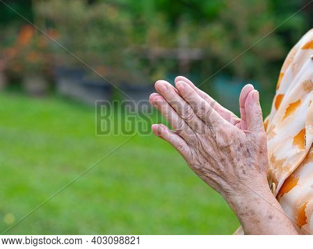 Close-up Of Senior Woman's Hands Joined Together For Praying While Standing In A Garden. Focus On Ha