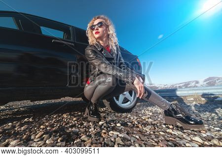 An Attractive Blonde In Sunglasses And Leather Clothes Sits Near A Black Sports Car On A Country Roa