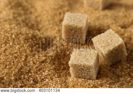 Brown Cane Sugar Crystals And Cubes Of Refined Cane Sugar Closeup.  Healthy Sweets Eating.