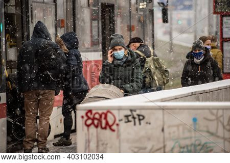 Prague, Czech Republic. 01-12-2021. People Walking After Descending From Tramway On A Snowing Day Wi