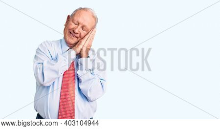 Senior handsome grey-haired man wearing elegant tie and shirt sleeping tired dreaming and posing with hands together while smiling with closed eyes.