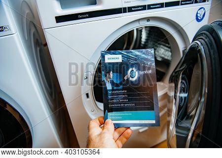 Paris, France - Jan 5, 2020: Pov Male Hand Holding Bosch Service Contact Flyer Advertising Informati