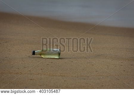Glass Bottle In Sand, Marina Beach, Chennai, India. Debris In The Beach