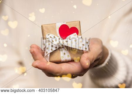 Beauty Woman Hands Holding Gift Box With Red Heart On Glow Bokeh Background, Close-up. Pastel Colors