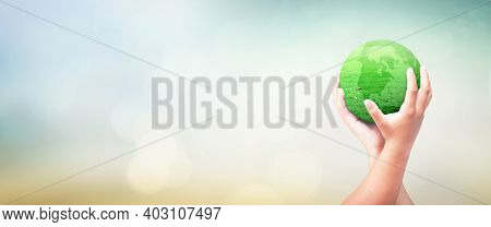 World Environment Day Concept: Human Hands Holding Earth Globe Of Grass Over Blurred Nature Backgrou