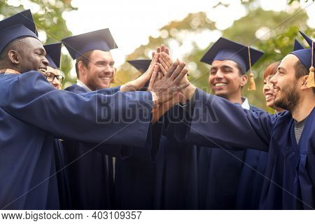 education, graduation and people concept - group of happy international graduate students in mortar boards and bachelor gowns making high five
