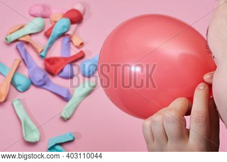 Woman Starts To Inflate A Balloon On A Pink Background.