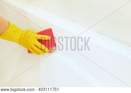 A Female Hand In A Yellow Rubber Glove With A Pink Sponge Washes And Polishes The Surface Of A White