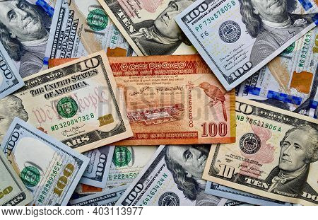 Sri Lankan Rupee On Top Of Usa National Currency, Top View Of Mixed American Dollars Banknotes. Lkr