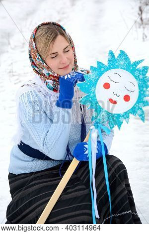 A Beautiful Young Woman In A Colored Shawl And Blue Mittens Sits With Closed Eyes On The Background