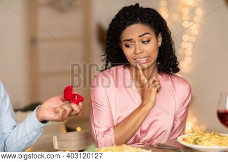 Proposal Failure. Confused African American Woman In Doubt Looking At Engagement Ring, Black Man Giv