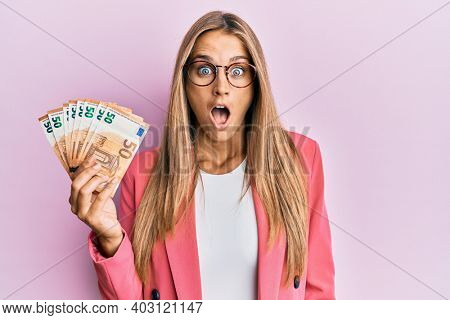 Young blonde woman wearing business style holding 50 euro banknotes scared and amazed with open mouth for surprise, disbelief face