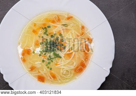 Vegetable Broth With Noodles. Homemade Soup On A White Plate.