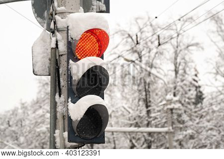 A Working Traffic Light On A City Street In Winter.the Red Light Of The Traffic Light Is On