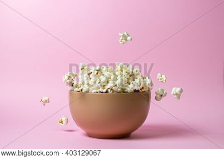 Popcorn On A Pink Background. A Full Plate Of Popcorn. Popcorn Falls Down. Movie Snack.
