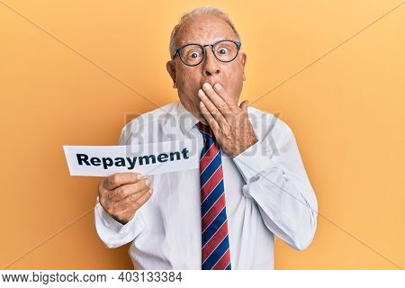 Senior caucasian man holding repayment word paper covering mouth with hand, shocked and afraid for mistake. surprised expression