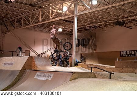 Bikers And Skaters Practice Tricks At Modern Skate Park During An Open Skate Session That Is Free To