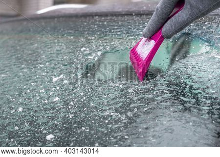 Woman's Hand Scrapes Ice Off The Windshield With A Pink Scraper Close-up