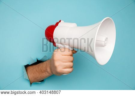 Mans Hand Arm Hold Megaphone Isolated Through Torn Blue Background