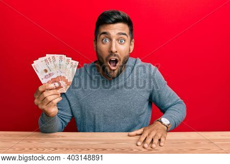 Handsome hispanic man holding colombian pesos scared and amazed with open mouth for surprise, disbelief face
