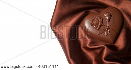 Chocolates Heart Shaped With A Pattern Of Flowers On Brown Silk.