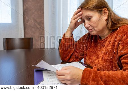 Pretty Desperate Adult Businesswoman Reviewing Bills At The Table In Her Living Room. Despair Concep