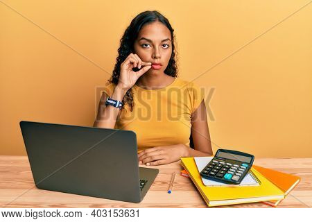 Young african american girl working at the office with laptop and calculator mouth and lips shut as zip with fingers. secret and silent, taboo talking