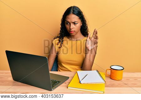 Young african american girl doing video call waving to laptop skeptic and nervous, frowning upset because of problem. negative person.