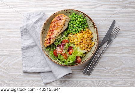 Baked Chicken Breast On Plate With Fresh Salad, Green Peas And Corn, White Wooden Background, Top Vi
