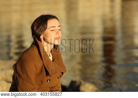 Relaxed Woman In Winter Breathing Fresh Air Sitting On The Beach At Sunset