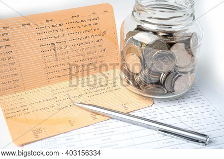 Pen On Account Book Bank With Coins In Glass Jar; Banking, Investment, Economy, Business Concept.