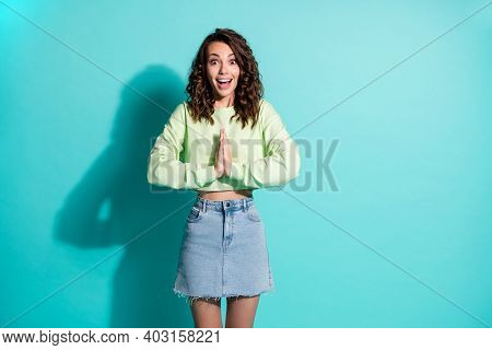 Photo Portrait Of Excited Girl Anticipating Holding Hands Together Isolated On Vivid Teal Colored Ba