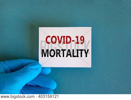 Covid-19 Mortality Symbol. Hand In Blue Glove With White Card. Concept Words 'covid-19 Mortality'. M