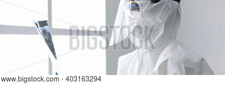 Doctor In Protective Overalls Holding X-ray Picture In Clinic. Doctor In Protective Overalls Holding