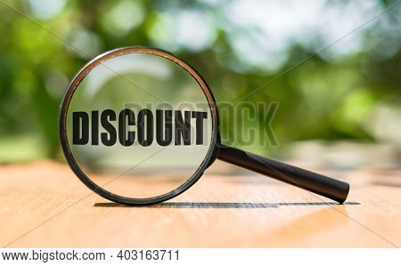 Magnifying Glass With Text Discount On Wooden Table And Green Background.