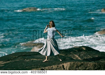 A woman is engaged in dances and choreography on the ocean coast.