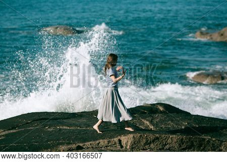 Woman is engaged in dances and choreography on the ocean coast.