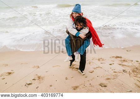 Happy young multiethnic couple on the beach holding tight piggyback ride