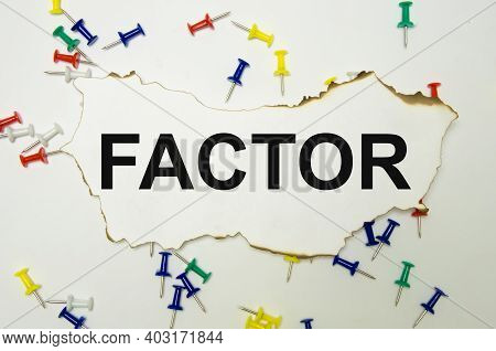 The Word Factor Is Written On A White Sheet Of Paper Which Lies On A White Background, Paper Clips L