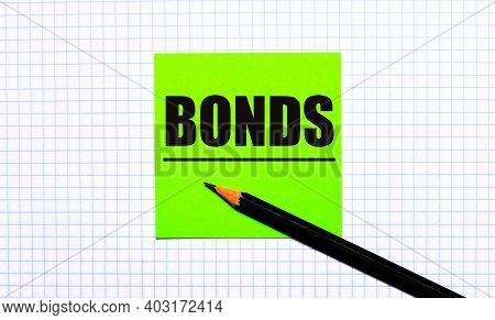 There Is A Green Sticker With The Text Bonds And A Black Pencil On The Checkered Paper.