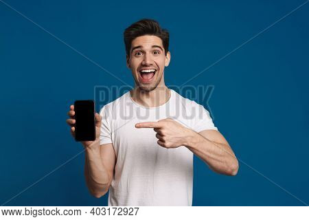 Delighted guy showing and pointing finger at mobile phone isolated over blue background