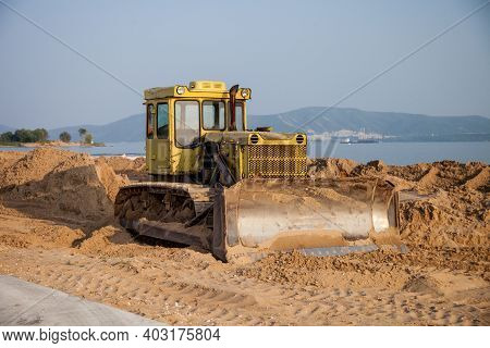 Tractor On The Beach Flattens The Sand